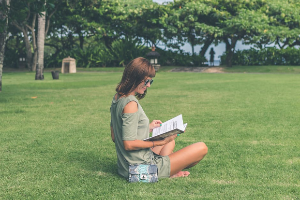 Woman reading outside on the grass.