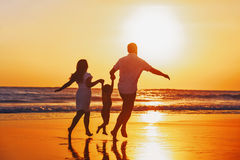 happy-family-child-have-fun-sunset-beach-father-mother-baby-son-hold-hands-run-along-edge-sea-black-sand-active-62355464.jpg